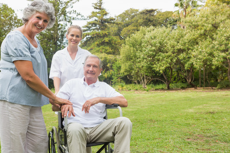 Cheerful man in a wheelchair with his nurse and wife smiling at camera in the park photo
