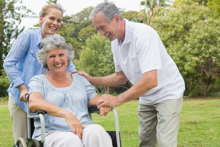 Happy woman in wheelchair with daughter and husband in the park laughing on sunny day photo