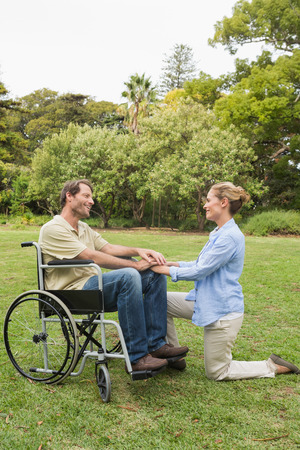 Happy man in wheelchair with partner kneeling beside him in the park on sunny day photo