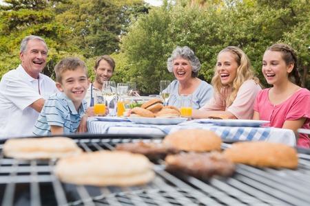 Laughing family having a barbecue in the park together looking at camera photo