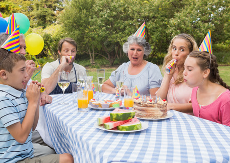 Family celebrating little girls birthday outside at picnic table blowing party horns photo