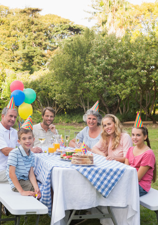 Happy family smiling at camera at birthday party outside at picnic table photo