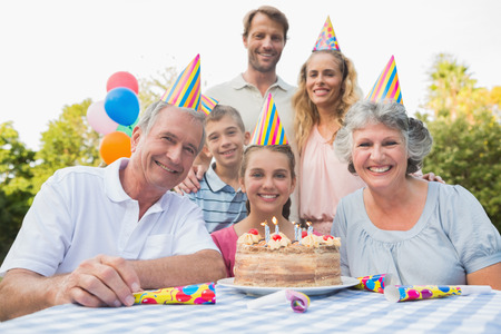 family picnic: Cheeful family smiling at camera at birthday party outside at picnic table Stock Photo