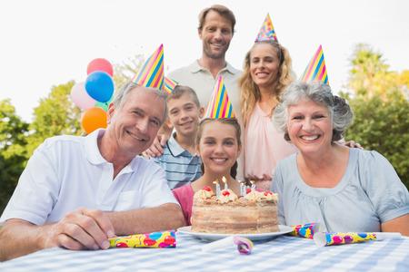 fiesta familiar: Familia Cheeful sonriendo a la c�mara en la fiesta de cumplea�os al aire libre en una mesa de picnic Foto de archivo
