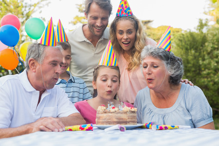 Cheerful extended family watching girl blowing out birthday candles outside at picnic table photo