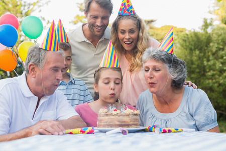 Happy extended family watching girl blowing out birthday candles at picnic table outside photo