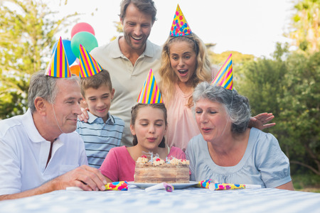 Happy extended family blowing out birthday candles together outside in the park photo