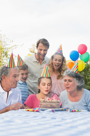 Cheerful extended family blowing out birthday candles together outside at picnic table photo