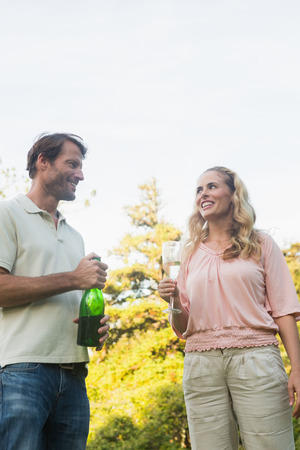 Beautiful couple having champagne together standing outside in sunshine photo
