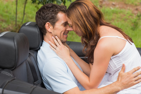 Young couple feeling romantic in back seat of convertible in countryside photo