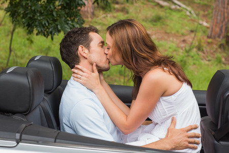 Beautiful couple kissing in back seat of a convertible photo