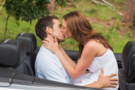 hombres besandose: Hermosa pareja bes�ndose en el asiento trasero de un convertible