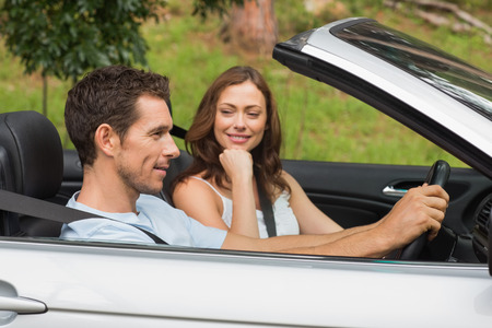 Young couple driving in a silver convertible through the countryside in sunshine photo