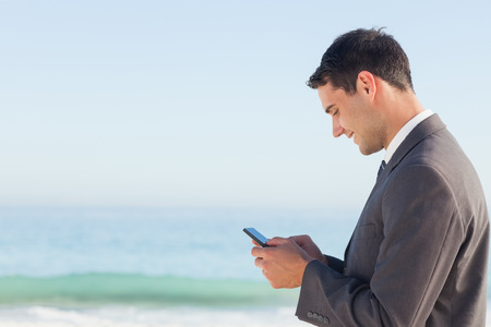 context: Smiling businessman  on the beach sending a text message Stock Photo