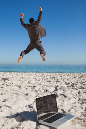 euphoria: Victorious businessman in suit jumping leaving his laptop on the beach