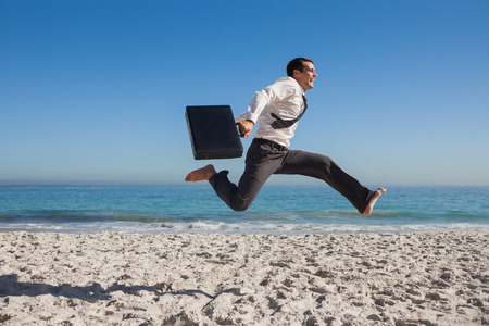 彼のブリーフケースを保持してビーチでジャンプ朗らかビジネスマン