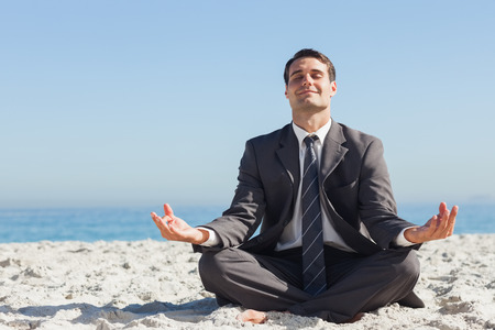 escapism: Young businessman sitting with legs crossed relaxing on the beach Stock Photo