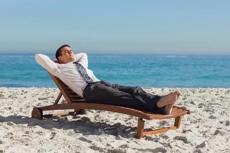 Giovane uomo d'affari di relax su una sedia a sdraio sulla spiaggia