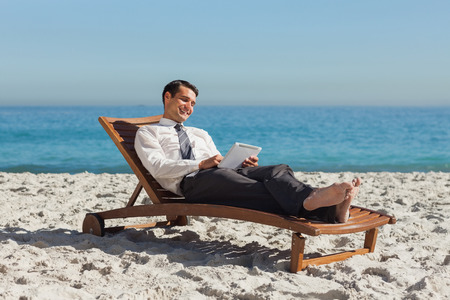 Young businessman  on the beach relaxing on a deck chair using his tablet photo