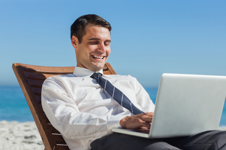 context: Happy young businessman on a deck chair using his computer on the beach Stock Photo