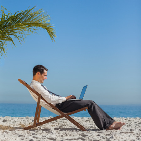Young businessman relaxing on his beach chair using his laptop photo