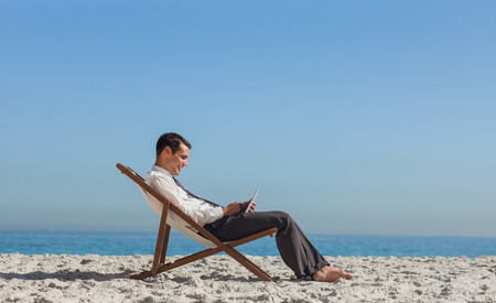 out of context: Young businessman on the beach resting on his deck chair using his tablet