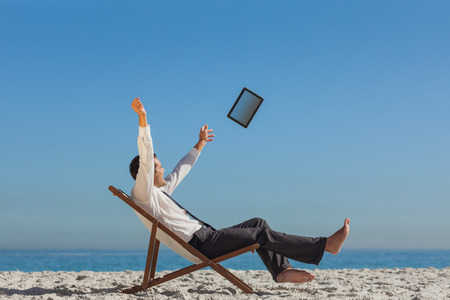 escapism: Victorious young businessman relaxing on his deck chair throwing his tablet away