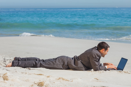 context: Young businessman relaxing lying on the sand typing on his laptop