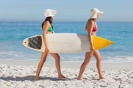 Two attractive women in bikinis holding a surfboard on the beach photo