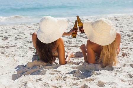 clinking: Atractiva rubia y morena, con sombreros de paja y botellas de vidrio que tintinean bikinis Foto de archivo