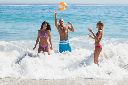 beachball: Happy friends playing with a beachball in the sea together Stock Photo