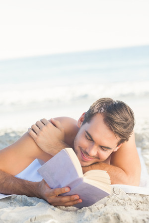 young man short hair: Smiling handsome man relaxing on the beach reading