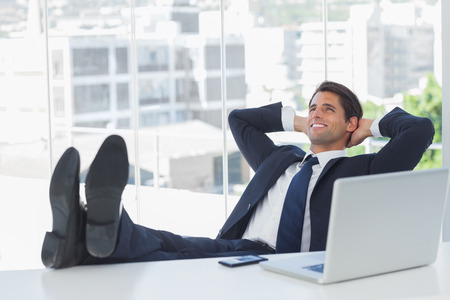 Successful businessman in his office relaxing with his feet on his desk Stock Photo