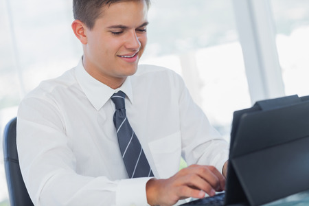 Cheerful young businessman working on his tablet pc in bright office photo