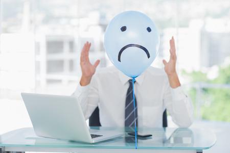 desolaci�n: Globo azul con la cara triste ocultar businessmans cara enojada en la Oficina brillante