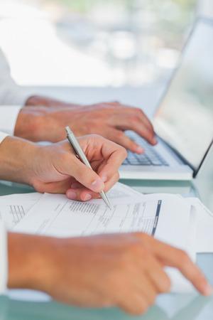 hombre escribiendo: Negocios que analiza documentos, mientras que otros trabajan en la computadora port�til Foto de archivo
