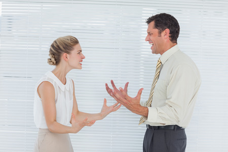 outraged: Angry business team having heated argument in bright office