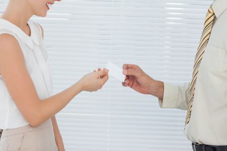 Businesswoman giving her business card to colleague in bright office