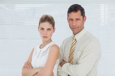 Frowning coworkers posing together in bright office photo