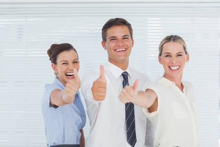 Smiling colleagues posing with thumbs up in bright office photo