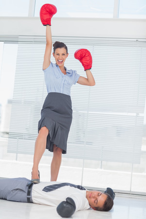 Businesswoman standing on defeated businessman wearing boxing gloves in bright office photo