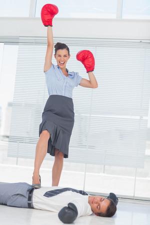 Femme d'affaires restant sur affaires battu avec des gants de boxe dans le bureau lumineux Banque d'images