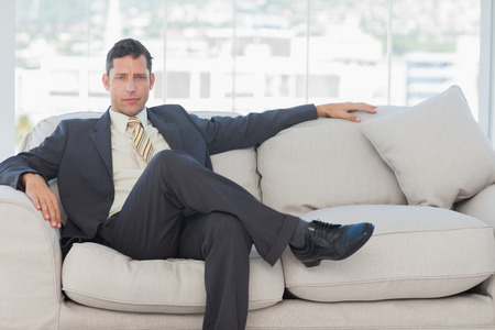 Serious businessman in suit posing sitting on sofa in bright office photo