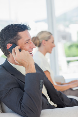 Cheerful businessman on the phone with his colleague working on computer in bright office photo