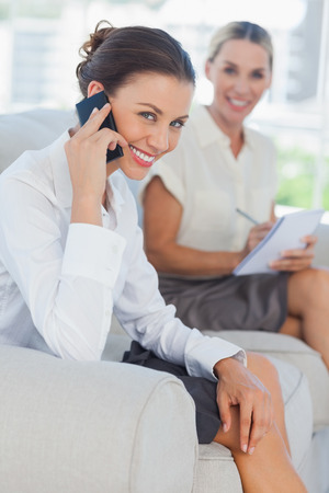 Businesswoman having a phone call while her colleague writing in bright office photo
