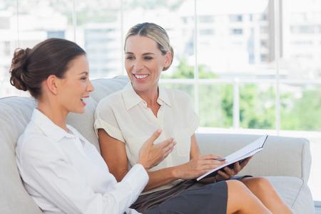 amigas conversando: Sonriendo empresarias hablando y trabajando juntos en la Oficina brillante Foto de archivo