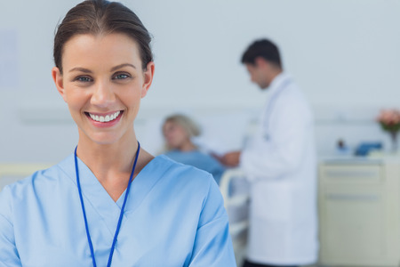 Cheerful surgeon posing in bright surgery with doctor attending patient on background photo