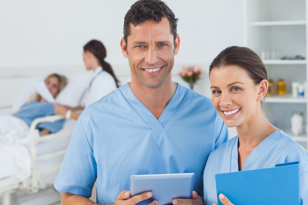 Portrait of surgeons in bright surgery with doctor attending patient on background photo