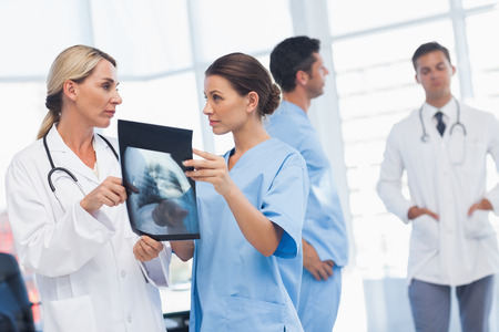 Surgeon and doctor analyzing x-ray together in medical office photo