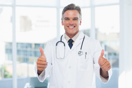 Experienced doctor posing thumbs up in medical office photo